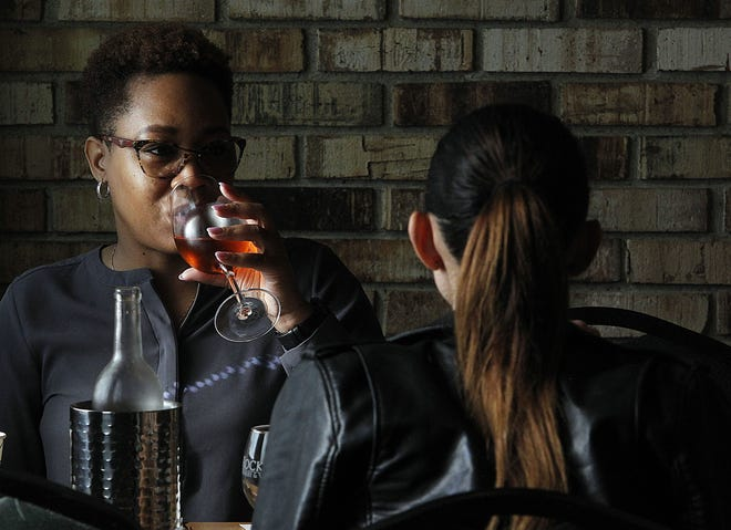 Jamila Mitchell (left) of Columbus Oxana Iabanji of Columbus enjoy a glass of wine April 29 at Wyandotte Winery in Columbus. Central Ohio wineries have faced the same challenges as restaurants and bars during the COVID-19 coronavirus pandemic, but the ones ThisWeek surveyed expect to return to vintage levels of business.