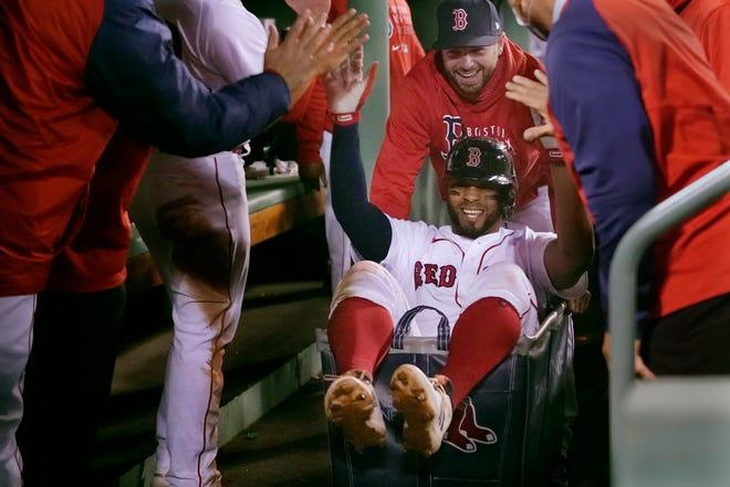 High-fives rekan setimnya dari Boston Red Sox Xander Bogaerts saat didorong dalam kereta cucian melalui ruang istirahat setelah dua run home run melawan Detroit Tigers selama inning kedua.