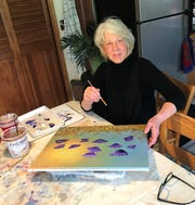 """Terry Lundahl works on a painting of a field of poppies in her home studio -- her kitchen table -- in Sturgeon Bay. Lundahl, who'd never taken up painting until she went through a series of unfortunate events last year, recently sold one of her poppy paintings for use on the upcoming Spectrum Originals cable TV show """"Joe Pickett."""""""