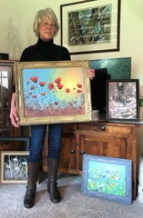 """Terry Lundahl shows some of her recent paintings in her Sturgeon Bay home. Lundahl, who'd never taken up painting until she went through a series of unfortunate events last year, recently sold one of her poppy paintings for use on the upcoming Spectrum Originals cable TV show """"Joe Pickett."""""""