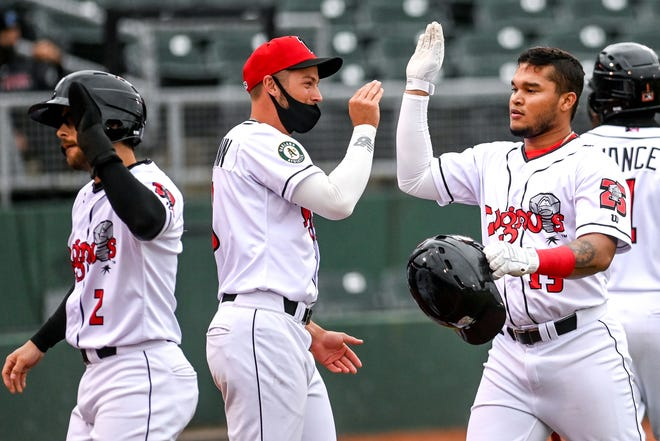 Lugnuts' Ryan Gridley, left, and Jordan Diaz, right, celebrate their runs against the Captains during the first inning on Tuesday, May 4, 2021, at Jackson Field in Lansing.