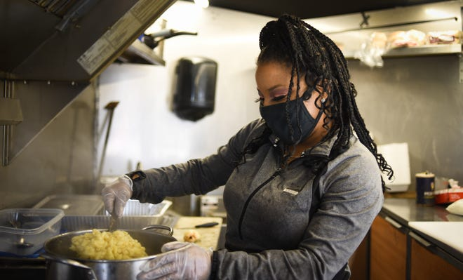 Krystal Jackson, owner of Krystal's Kitchen prepares her signature macaroni and cheese, Wednesday, May 5, 2021, at her food trailer in the Menard's parking lot on Lansing's southside.  Specializing in BBQ, Jackson says she's actually seen an increase in business throughout the pandemic.