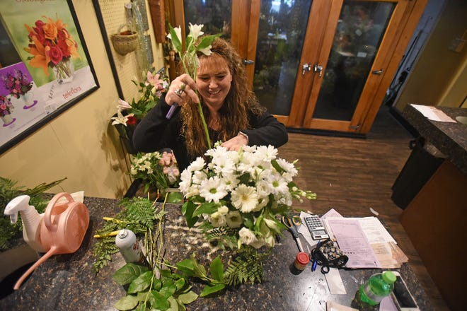 Tara Beaire, the owner of Tara's Floral Expressions at 48 W. Fourth Street, makes a daisy bouquet Wednesday morning.