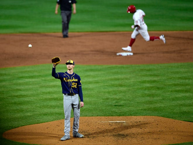 Brewers starting pitcher Eric Lauer receives a new ball after giving up a home run to the Phillies' Andrew McCutchen during the third inning Tuesday night.