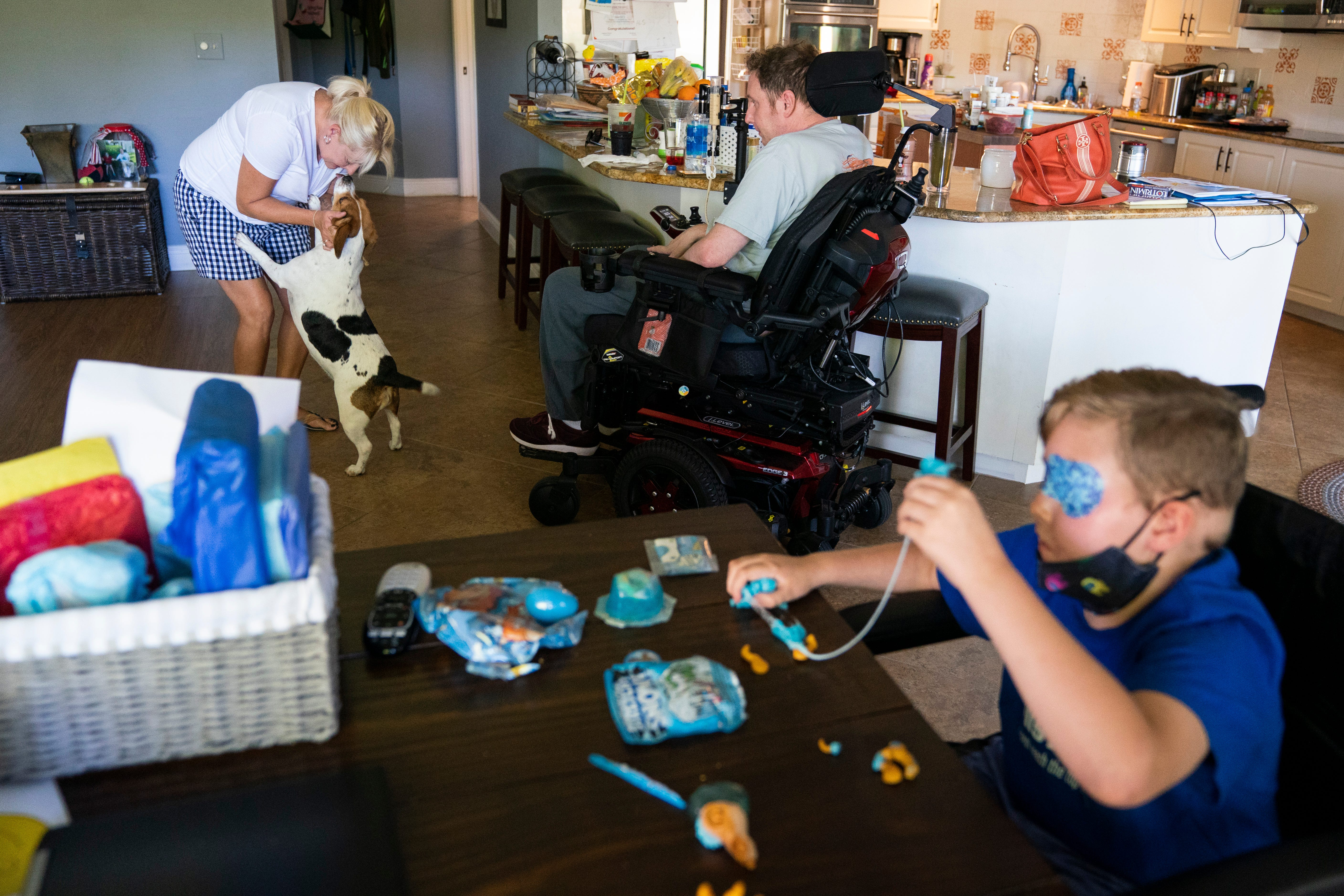 """Gay Valimont, left, pets Daisy, the family beagle, while her husband Brian Valimont, center, watches and their son Eli Valimont, 8, right, plays with slime at their home in North Naples on Friday, April 30, 2021. The Valimonts' lives have changed drastically over the past year — Brian was diagnosed with ALS in August of 2020 and a few months later, Eli was diagnosed with DIPG, an incurable brain tumor that begins in the brain stem. Despite the grief and stress, Gay cherishes every moment she has with her family. """"Take every moment and love each other,"""" she said."""
