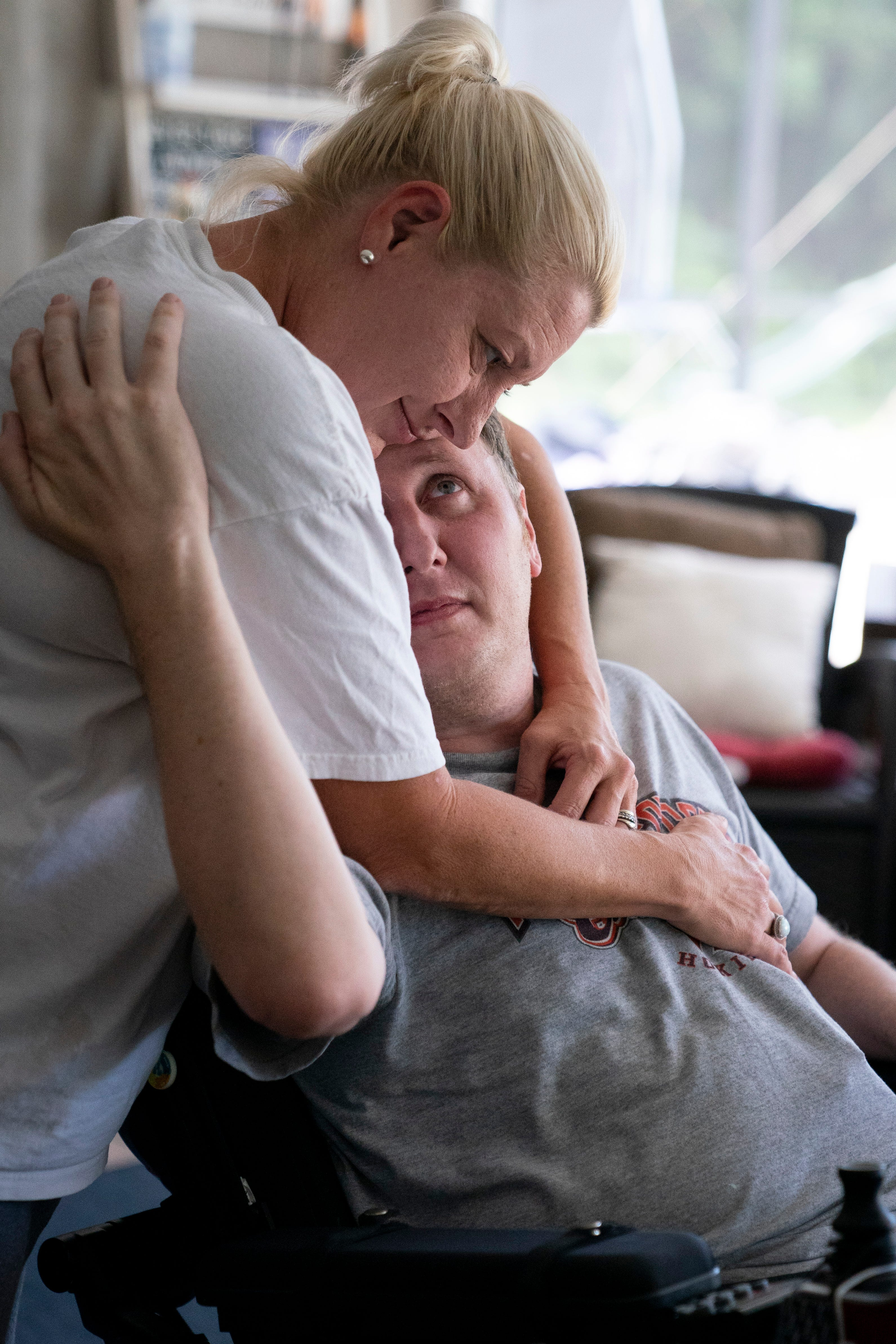"""Brian looks up at Gay as they hug at their home in North Naples on Tuesday, May 4, 2021. """"I think the night I met Gay my soul recognized hers,"""" Brian wrote."""