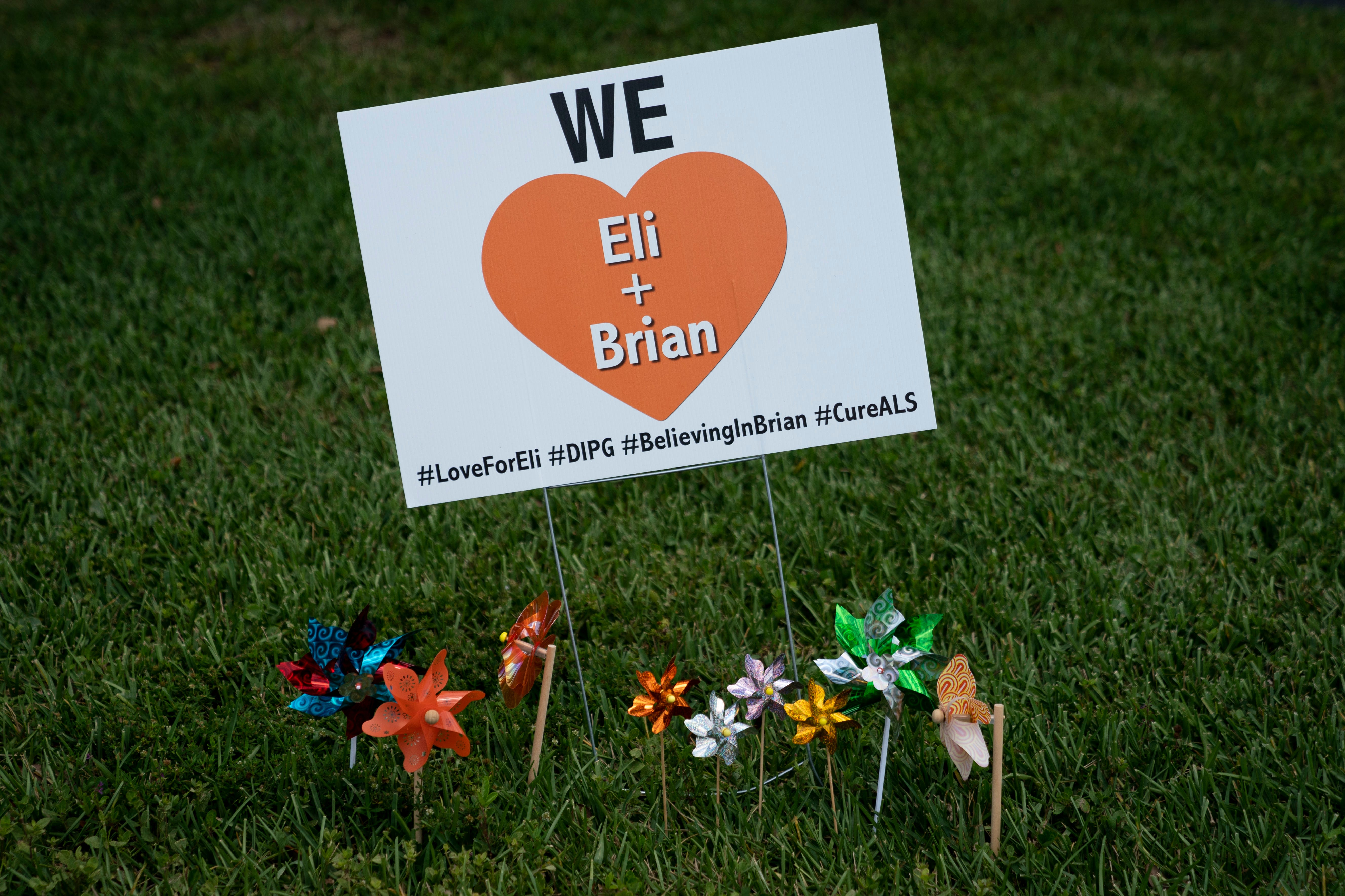 Pinwheels blow in the breeze as they surround a sign showing support for Eli and Brian placed on the lawn of one of the Valimonts' neighbors in North Naples on Tuesday, May 4, 2021. The signs have cropped up in yards all around Palm River Estates, from the neighborhood's entrance all the way to the Valimonts' street.