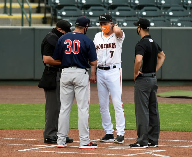 Delmarva Shorebirds manager Dave Anderson (7) meets with Salem Red Sox manager Luke Montz (30) at home plate Tuesday, May 4, 2021, at Perdue Stadium in Salisbury, Maryland.
