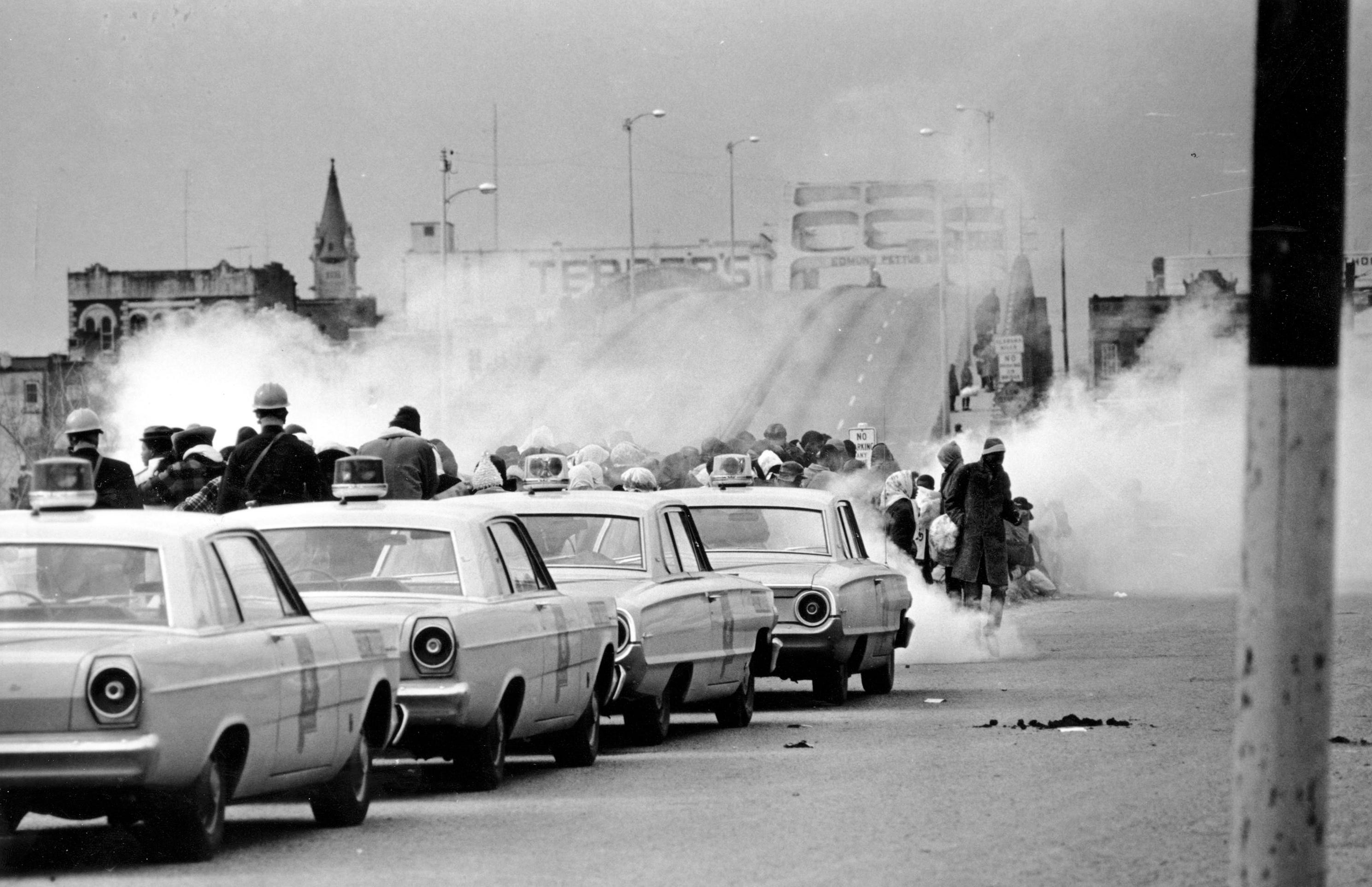 """In this March 7, 1965 file photo, clouds of tear gas fill the air as state troopers, ordered by Gov. George Wallace, break up a demonstration march in Selma, Ala., on what became known as """"Bloody Sunday."""""""