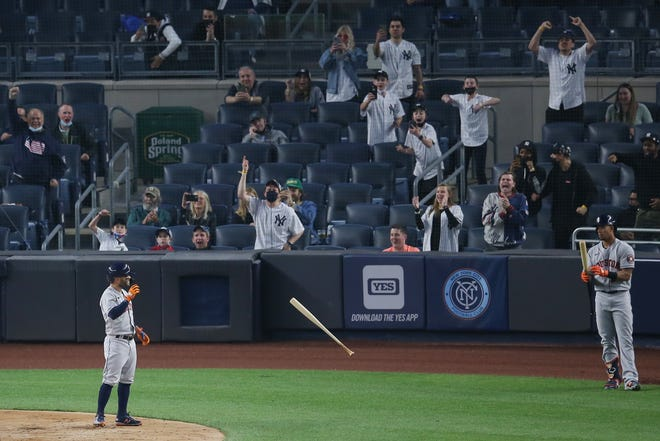 New York Yankees fans react as Houston Astros second baseman Jose Altuve tosses his bat after striking out to end the top of the third inning.