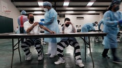 Prisoners at the Bolivar County Correctional Facility in Cleveland, Mississippi receive a Covid-19 vaccination administered by medical workers with Delta Health Center on April 28, 2021. The prisoners, part of a population particularly vulnerable to Covid-19, are given a choice between the one-shot Johnson & Johnson vaccine and one from Moderna. (Photo by Spencer Platt/Getty Images)