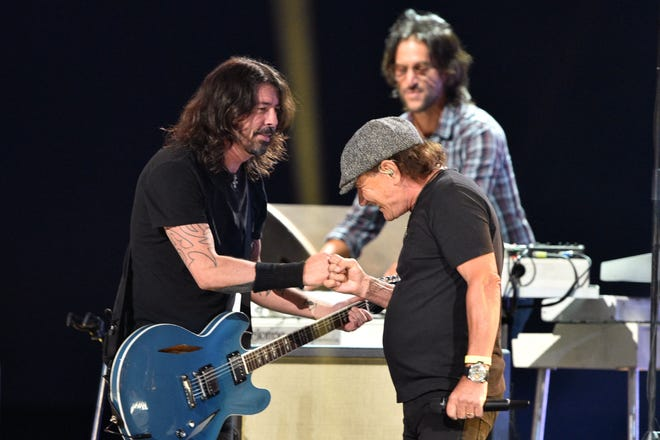"""AC/DC singer and Sarasota resident Brian Johnson bumps fists with Dave Grohl of the Foo Fighters after performing the AC/DC classic """"Back in Black"""" with them onstage during the taping of """"Vax Live: The Concert to Reunite the World."""""""
