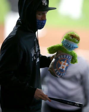 A New York Yankees fan holds an Oscar the Grouch doll that sits in a Houston Astros trash can.