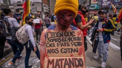 """A protester holds a sign, which, translated to English, reads: """"They say we are the future of the country but they are killing us,"""" on May 5, 2021 in Bogota, Colombia."""