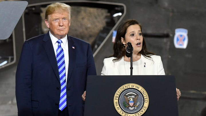 President Donald Trump, left, listens as Rep. Elise Stefanik, R-N.Y., speaks before signing a $716 billion defense policy bill at Fort Drum, N.Y. on Aug. 13, 2018.