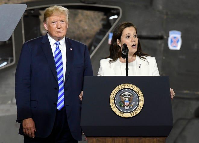 President Donald Trump, left, listens as Rep. Elise Stefanik, R-N.Y., speaks before signing a $716 billion defense policy bill at Fort Drum, N.Y. on Aug. 13, 2018.