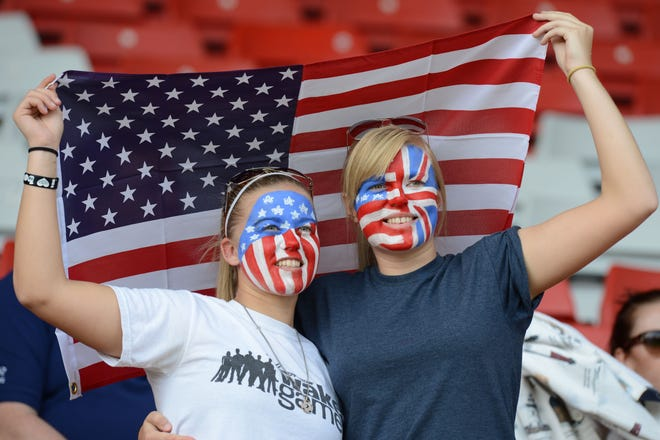 Fans of the U.S. women's soccer team hold up their flag during the 2012 London Olympics. No international fans will be allowed at the Tokyo Games due to COVID-19 restrictions.