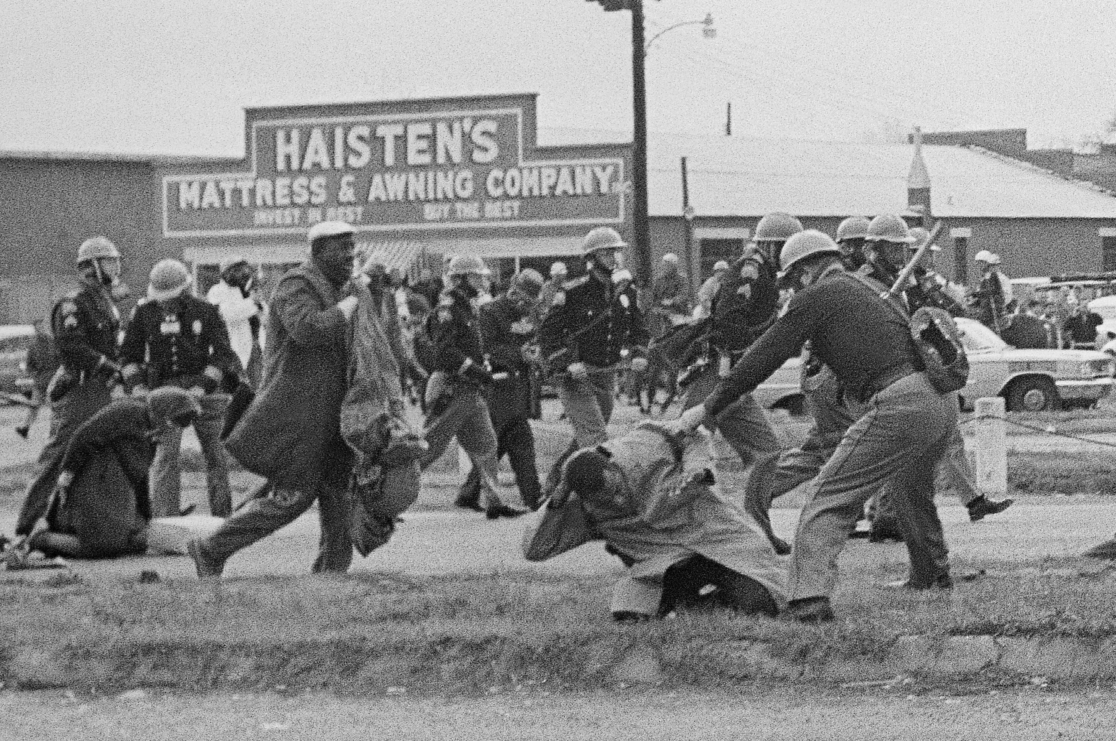In this March 7, 1965, file photo, a state trooper swings a billy club at John Lewis, right foreground, chairman of the Student Nonviolent Coordinating Committee, to break up a civil rights voting march in Selma, Ala