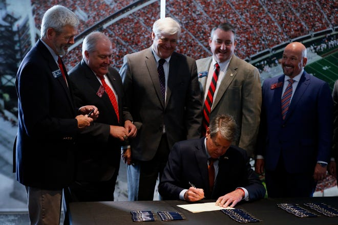 Georgia Gov. Brian Kemp signs legislation allowing student-athletes to control and earn money off  their name, image and likeness during a ceremony at the University of Georgia's Sanford Stadium.