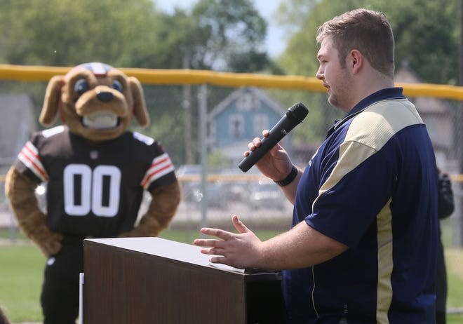 Chomps, a Browns mascot, listens to Colton Burkhart, an Archbishop Hoban High School student athlete, during a ceremony during which the Browns dedicated a new turf field to the school on Thursday  The new synthetic turf fields will be installed over what was once grass fields, and be called the Wentz Financial Family Fields. The project at Hoban is the Browns' 11th field installment in the past five years. [Mike Cardew/Beacon Journal]
