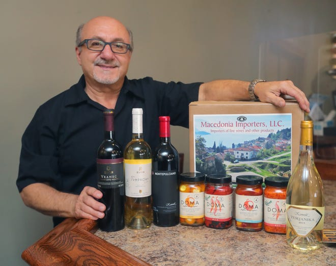 Village Gardens owner Tommy Metlovski shows off some of the imported peppers and wines served in his State Road restaurant in Cuyahoga Falls.