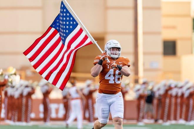 Texas linebacker Jake Ehlinger carries the American flag onto the field before the 2019 season opener against Louisiana-Lafayette. Ehlinger, the younger brother of former UT quarterback Sam Ehlinger, was found dead Thursday in Austin. He was 20.
