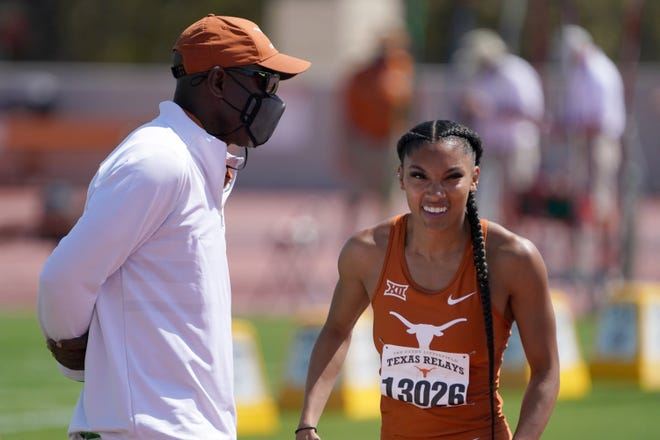 Texas track coach Edrick Floréal talks with Tara Davis during the women's long jump at the Texas Relays in March. Davis set a collegiate record with a jump of 23-5¼. It's the fifth-longest jump in U.S. history and the longest in the world this year.