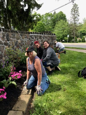 Members of the Alliance Garden Club plant flowers at the entrance to Silver Park.