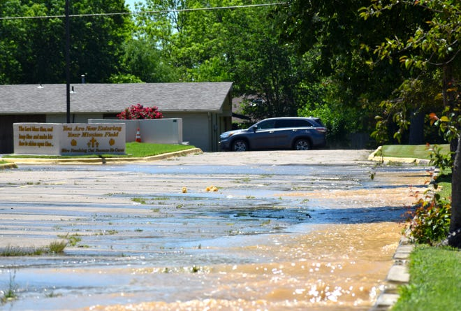 Water flows from an underground water leak in the parking lot of Crystal Rock Cathedral Thursday, May 6, 2021. A water main leak along the road completely saturated the ground beneath the nearby parking lot.