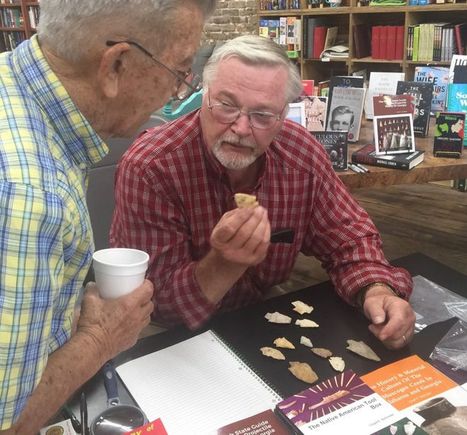 """Author Lloyd Schroder (at right) holds a projectile point from the collection of Leon Perry (at left) of Tennille. Perry said he found his artifacts in Washington County. Schroder said the point he holds is about 8,000 years old and is a Kirk corner notch. Schroder was at Broad Street Books in April to sign copies of his book, """"The Peach State Guide to the Projectile Points of Georgia."""""""