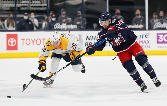Columbus Blue Jackets right wing Oliver Bjorkstrand (28) scores an empty-net goal, his second of the game, ahead of Nashville Predators right wing Eeli Tolvanen (28) during the third period of the NHL hockey game in Columbus on Wednesday, May 5, 2021. The Blue Jackets won 4-2.