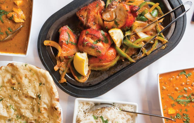 Chicken tandoori (center) with (clockwise from bottom right) matar paneer, rice, naan and chicken curry from Amul India