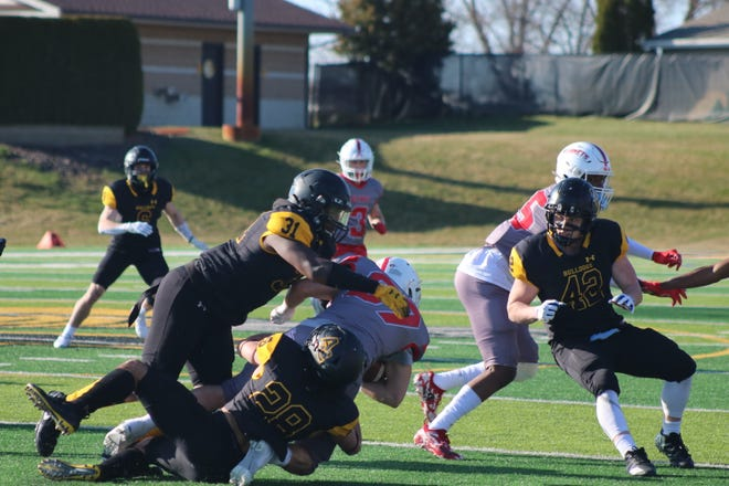 Adrian College's DeAndre Jennings (31) and Dominic Wood (28) make a tackle as Kyle Minder (42) closes in for the assist during the Bulldogs' game against Olivet on April 2.