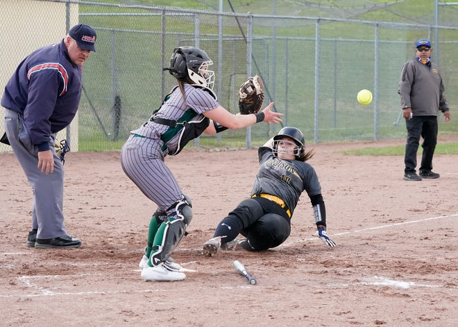 Madison's Annie McDade (18) slides into home plate as Sand Creek catcher Emma Reckner reaches for the throw during Wednesday's TCC doubleheader at Madison.