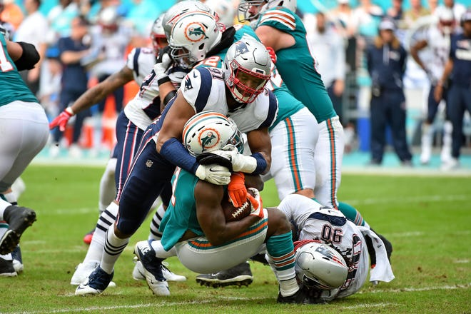 Dec 9, 2018; Miami Gardens, FL, USA; New England Patriots defensive end Deatrich Wise (91) tackles Miami Dolphins running back Frank Gore (21) during the first half at Hard Rock Stadium.