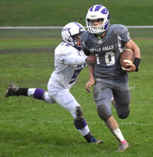 West Canada Valley's Dominick Coriale grabs Little Falls Mountie Zack McKoy (10) from behind on a punt return during the second quarter of Wednesday's game.