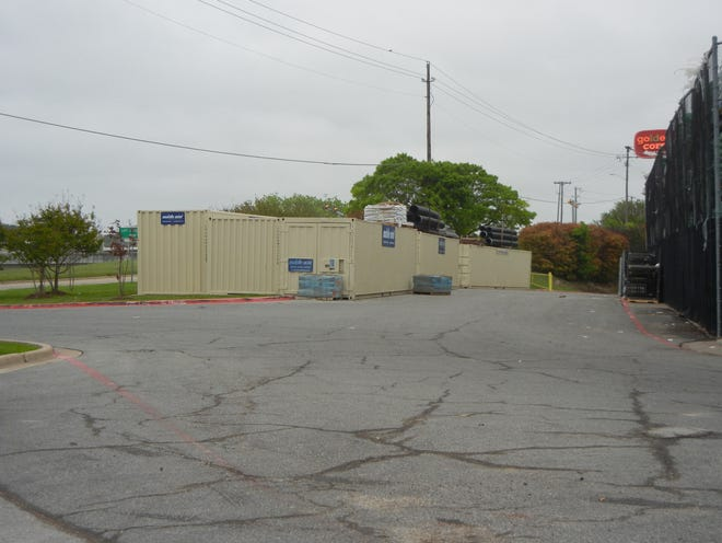 A series of shipping containers sit beside a business in Sherman along U.S. Highway 82. The city of Sherman is considering an ordinance change that would allow for use of these containers for storage on a temporary basis only.