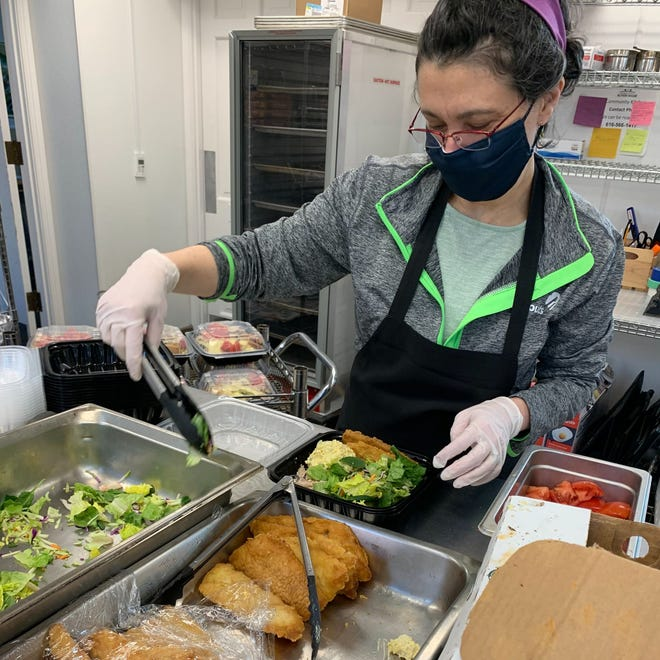 A volunteer assembles meals for Community Action House in Holland. Throughout the month of June, a cohort of Herman Miller retirees will rally support for the nonprofit.