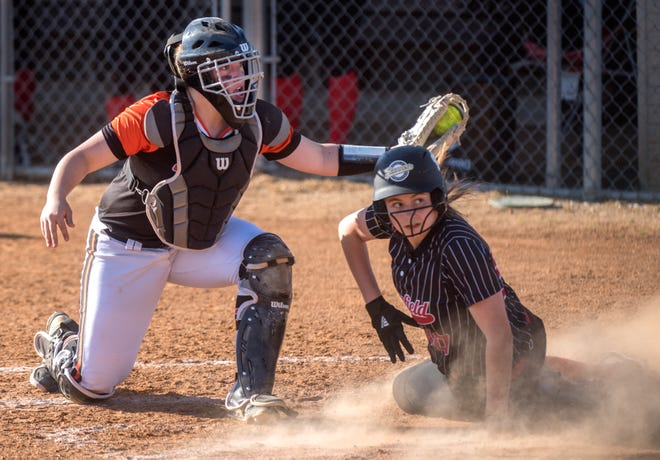 Illini Bluffs catcher Kristen Graham, left, and Brimfield baserunner Kierra Johnson look for the ump's call after a play at the plate in the seventh inning of a game this month at Brimfield High School. Johnson was out on the play and Illini Bluffs went on to win 8-3.
