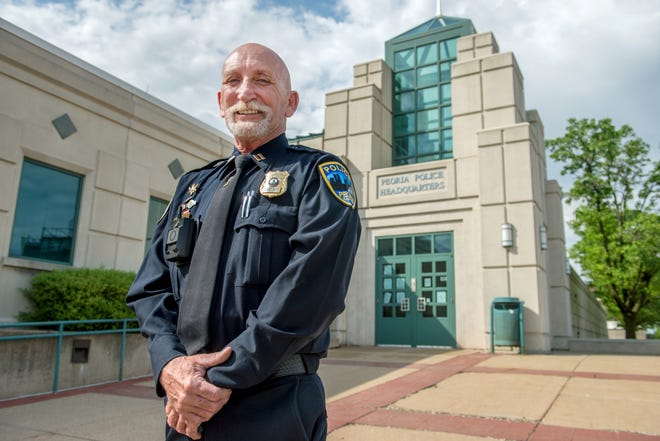 Peoria police Capt. Mike Scally poses in front of the Peoria Police Department headquarters at 600 SW Adams St. in Peoria. The veteran officer is retiring after 43 years.