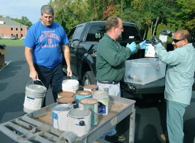 John Ansara (left) of Lambertville brings several paint items to a Household Hazardous Waste Collection and Secure Document Shredding Event held at the Bedford Government Center in Temperance in 2012. Helping him unload are Skip James and Marcol Esgeban from Environmental Enterprizes from Cincinnati, Ohio.