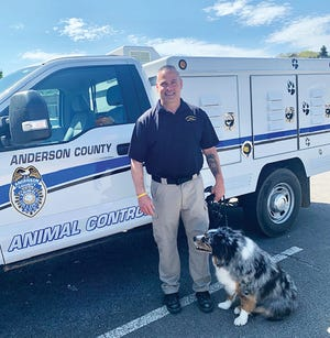 Paul Rehn, one of Anderson County's newest animal control officers, is pictured with his dog, Jake, standing beside his work truck that shows the new department emblem. Special to The Oak Ridger