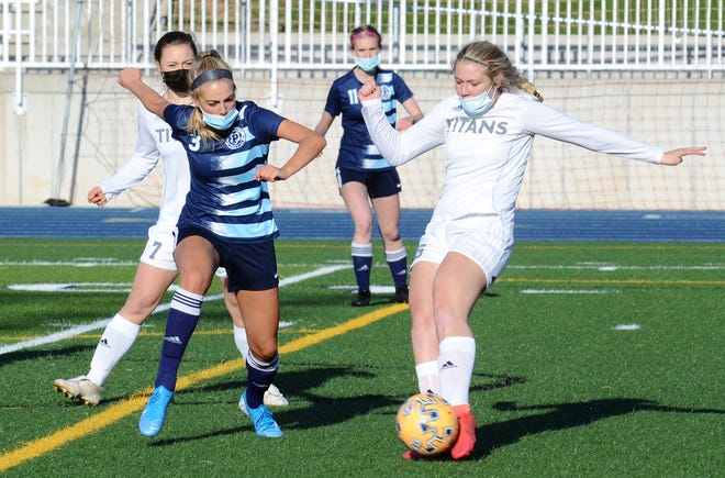 Petoskey's Molly Anderson (left) runs in to disrupt a clearing by TC West's Kaylee Niezgoda during the first half.