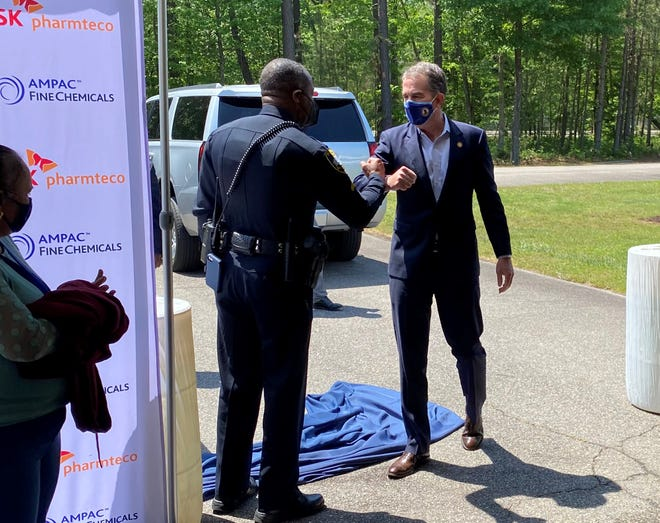In this May 4, 2021 file photo, Virginia Gov. Ralph S. Northam, right, fist-bumps a Petersburg Police officer upon arrival to the AMPAC Fine Chemicals plant in Petersburg.