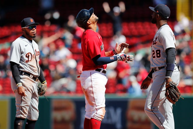 Boston Red Sox's Xander Bogaerts, center, celebrates His RBI single between Detroit Tigers' Harold Castro, left, and Niko Goodrum (28) during the fourth inning of a baseball game, Thursday, May 6, 2021, in Boston. (AP Photo/Michael Dwyer) ORG XMIT: NYOTK
