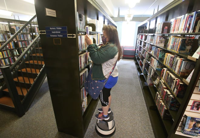 Amy Anderson looks for a book in the inspirational section at the Massillon Public Library.