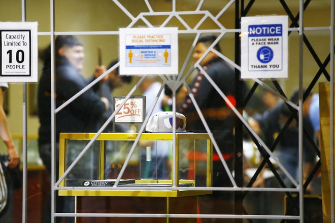 Men clean up inside Soto's Jewelry after the store was burglarized on May 30, 2020, in Rockford. This week, charges were authorized against two men in connection to the burglary.