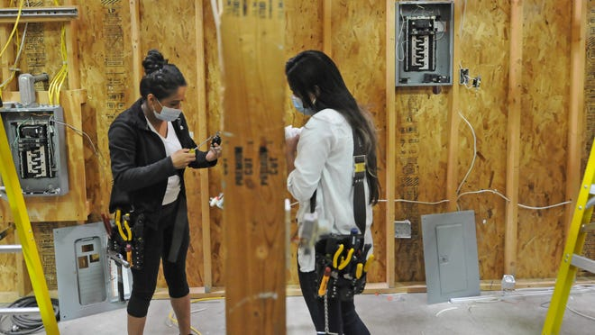 Twins Marcelle Cruz, left, and Beronica Cruz practice wiring a four-way lighting system inside the electrical department at the Salina Area Technical College last semester.