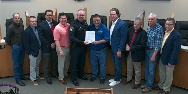 Mayor Doug Svien, center, presents a proclamation to Stephenville Police Chief Dan Harris as the other city council members look on during Tuesday's regular city council meeting. The proclamation declares April 28 Sgt. Steven Watts day in Stephenville, in honor of a longtime SPD officer who died recently unexpectedly after a short illness.
