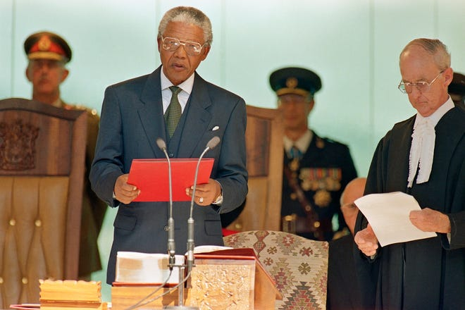 Nelson Mandela reads the oath of office on May, 10, 1994, at the Union Building in Pretoria as he is sworn in as president of South Africa. Mandela was the first black president in the history of the republic.